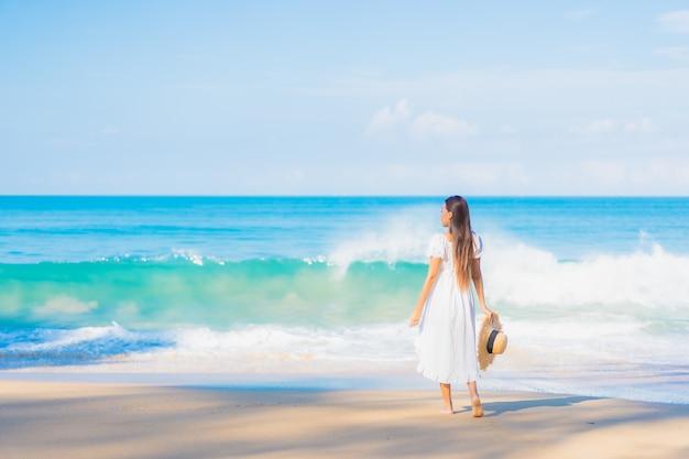 여행 휴가에 푸른 하늘에 흰 구름과 해변 주변에서 편안한 아름 다운 젊은 아시아 여자의 초상화 무료 사진