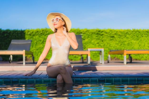 호텔 리조트에서 야외 수영장 주변에서 편안한 아름 다운 젊은 아시아 여자의 초상화 무료 사진
