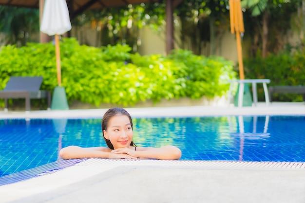 ホテルリゾートの屋外スイミングプールの周りでリラックスした美しい若いアジアの女性の肖像画 無料写真
