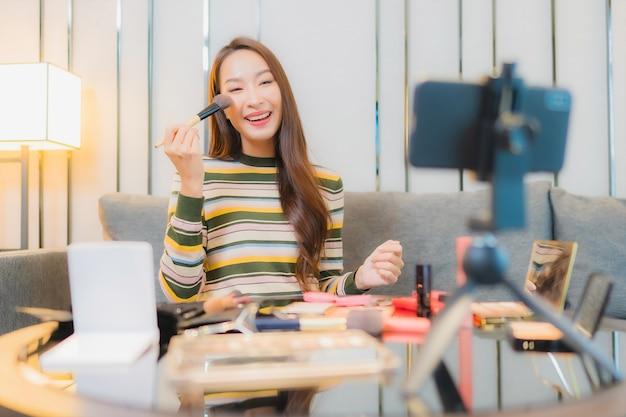 美しい若いアジアの女性の肖像画は、ソファの上の化粧品をレビューし、使用しています 無料写真