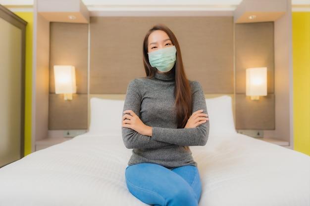 Портрет красивой молодой азиатской женщины носит маску в спальне Бесплатные Фотографии