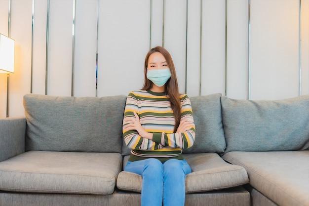 美しい若いアジアの女性の肖像画は、リビングルームのインテリアのソファにマスクを着用 無料写真