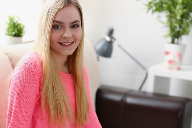 Портрет красивой молодой блондинкой сидеть на диване в комнате рано утром Premium Фотографии