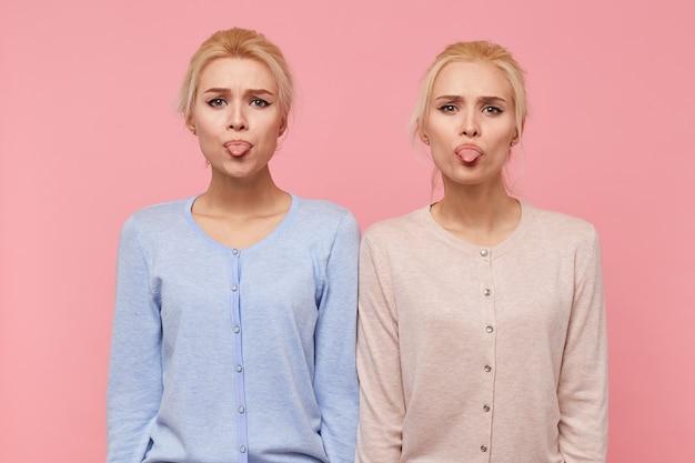 ピンクの背景の上に分離されたカメラを見て、美しい若い金髪の双子の肖像画は顔を作り、舌を表示します。 無料写真