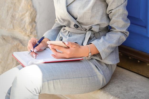 문 앞에 휴대 전화와 메모장에 앉아 아름 다운 젊은 백인 비즈니스 여자의 초상화 프리미엄 사진