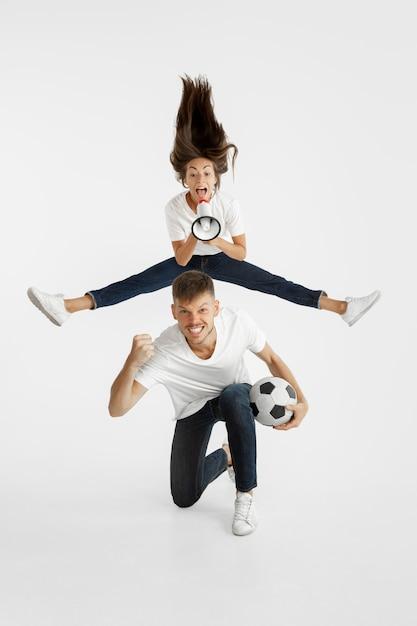 美しい若いカップルのサッカーやサッカーファンの肖像画。顔の表情、人間の感情、広告、スポーツのコンセプト。女性と男性がジャンプし、叫び、楽しんでいます。 無料写真