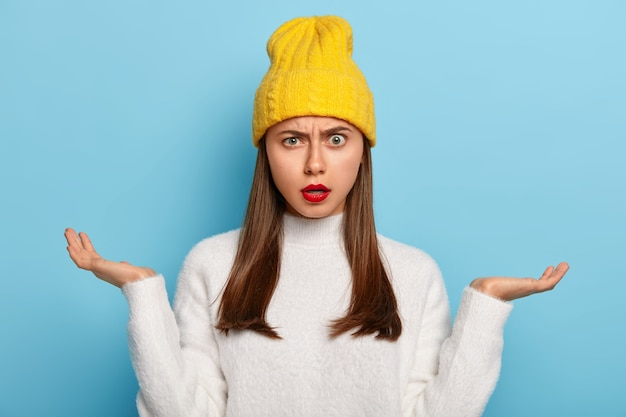 Портрет красивой молодой девушки, которую допрашивают, раскладывает ладони в стороны, чувствует неосознанность и сомнение, носит красную помаду, носит стильную желтую шляпу, белый джемпер Бесплатные Фотографии