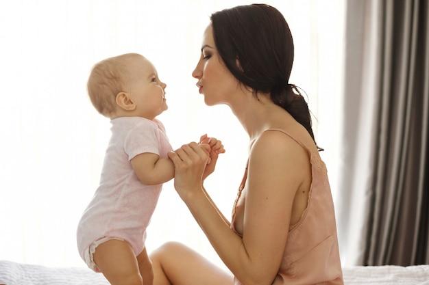 パジャマとベッドのウィンドウの表面に座ってお互いを見ている彼女の赤ちゃんの美しい若いお母さんの肖像画。 無料写真