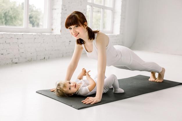 흰색 스포츠에서 아름 다운 젊은 어머니의 초상화는 검은 매트에 운동을하는 그녀의 매력적인 작은 여자 아기와 함께 착용 프리미엄 사진