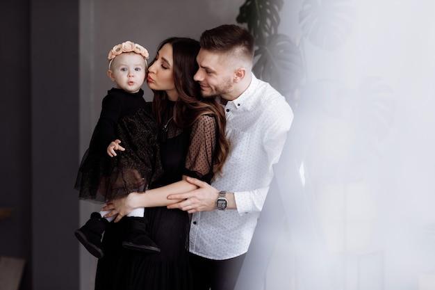 Портрет красивых молодых родителей и их милая маленькая дочь обнимает и улыбается в помещении. день матери, отца, ребенка. понятие семьи. семейный вид Premium Фотографии
