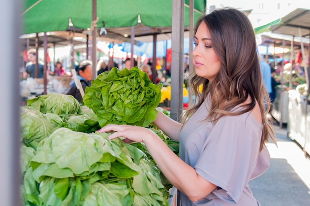 Portrait of beautiful young woman choosing green leafy vegetables  in green market. Concept of healthy food shopping. Young woman buying vegetables at the green market. Free Photo