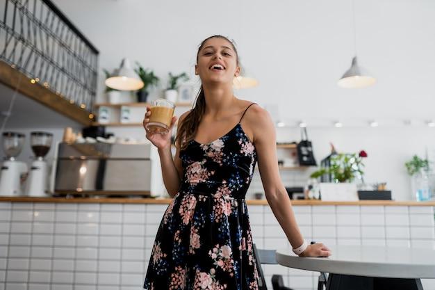 朝コーヒーを飲みに行く美しい若い女性の肖像画 無料写真