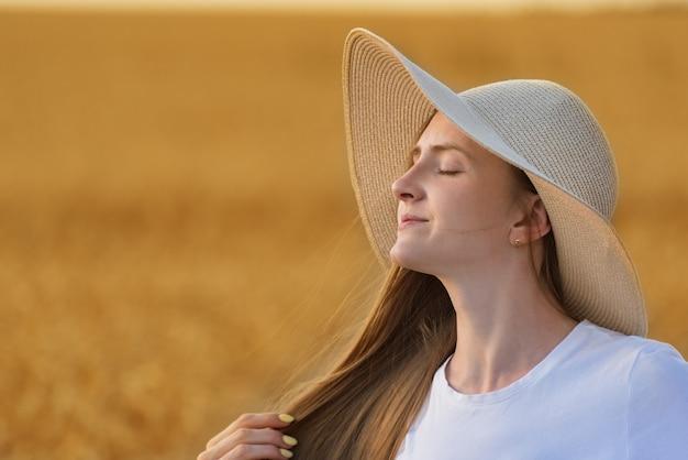 Портрет красивой молодой женщины в шляпе на теплой нейтральной предпосылке. Premium Фотографии