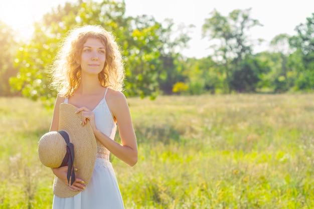 美しい若い女性の肖像画は立って、太陽光線でファッショナブルな帽子に笑みを浮かべてください。白いドレスのロマンチックな女の子は歩いて、夕暮れ時の広々としたフィールドで夢を見ています。プロヴァンス風。 Premium写真