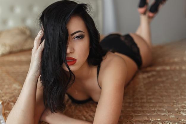 그녀의 속옷에 침대에 누워 아름 다운 젊은 여자의 초상화. 프리미엄 사진