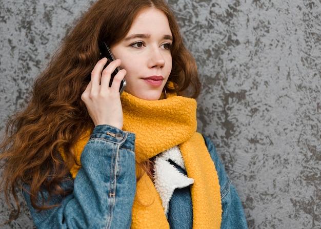 Портрет красивой молодой женщины разговаривает по телефону Бесплатные Фотографии