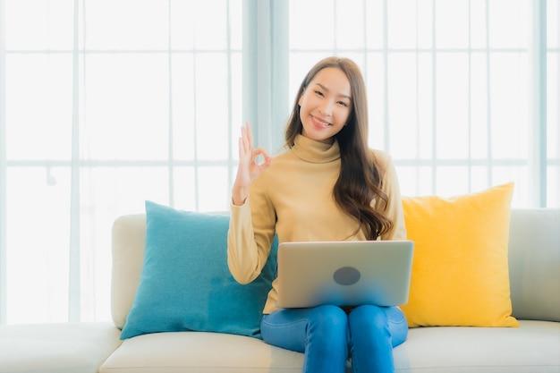 Портрет красивой молодой женщины, использующей ноутбук на диване в гостиной Бесплатные Фотографии