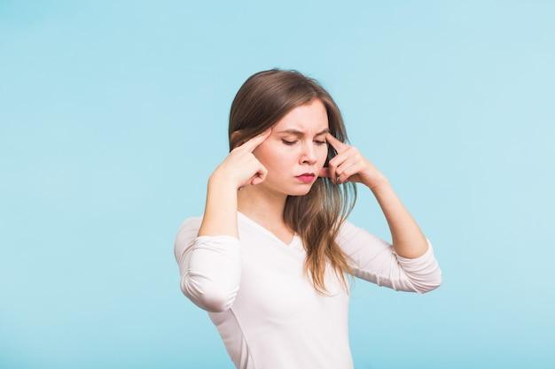 Портрет красивой молодой женщины с голыми плечами, касающейся ее висков, чувствуя стресс, на синем Premium Фотографии