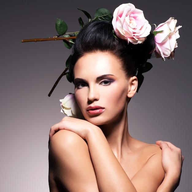 髪のポーズの花と美しい若い女性の肖像画 無料写真