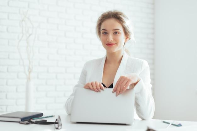 Портрет красивой молодой женщины, работающие в офисе. Premium Фотографии