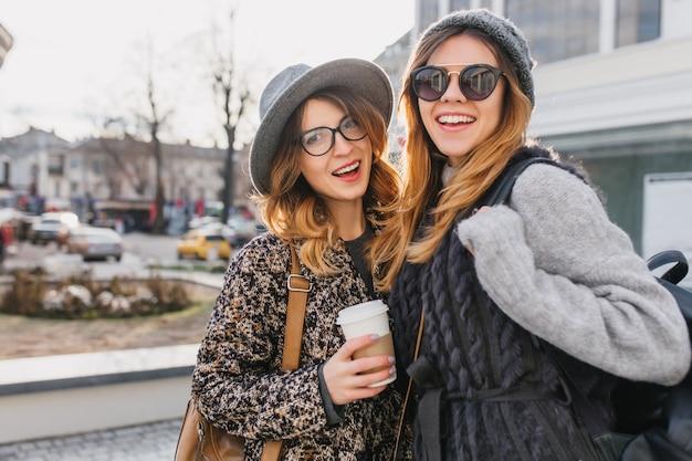Портрет блаженных женщин, гуляющих вместе холодным утром и позирующих снаружи с чашкой кофе. удивительная молодая женщина в модном пальто и солнцезащитных очках проводит время с другом на главной улице. Бесплатные Фотографии
