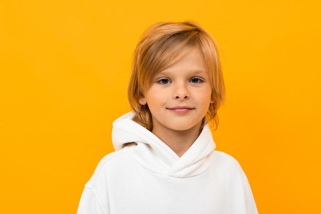 黄色のスタジオのクローズアップに顔をゆがめた金髪の少年のポートレート Premium写真