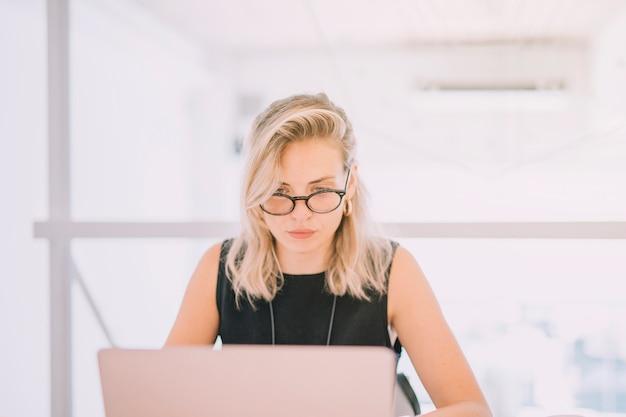ノートパソコンを見て金髪の若い実業家の肖像画 無料写真