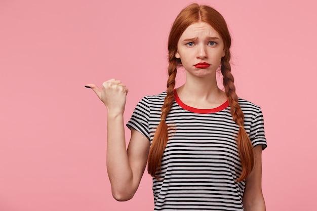 青い目の若い赤い髪の少女の肖像画は、ピンクの壁に、何かに不満、唇のふくれっ面、侮辱を表現、悲しみ、動揺、欲求不満、空白のコピースペースの左側を親指で指しています 無料写真