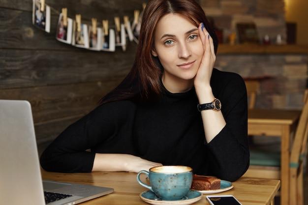 一方で黒い服を着て傾いている黒い服で退屈若い白人女性の肖像画 無料写真