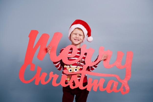 クリスマスのレタリングを持つ少年の肖像画 無料写真