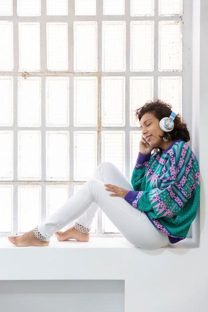 窓に座って音楽を聴いているブルネットの少女の肖像画。テキスト用のスペース。 Premium写真