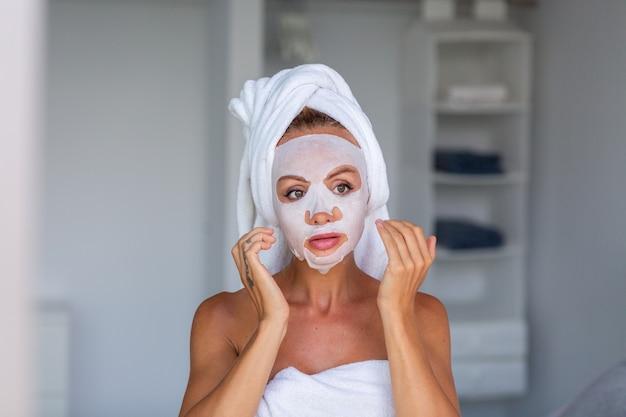 머리에 수건과 얼굴에 화장품 마스크와 진정 백인 예쁜 여자의 초상화 얼굴 피부 관리 개념 여성 집에서 침대에서 휴식 무료 사진