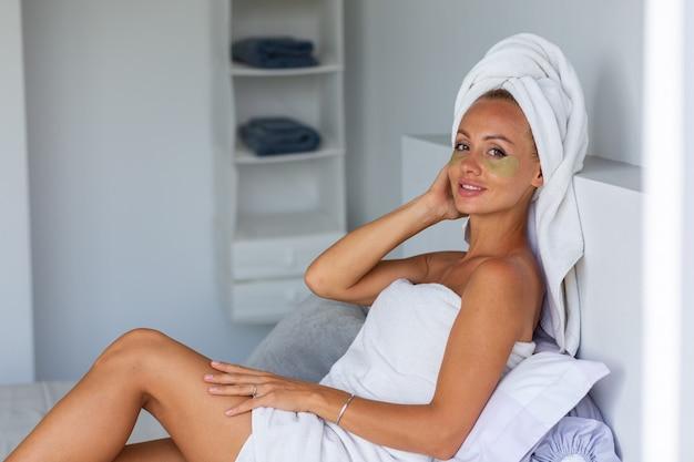 얼굴에 머리와 눈 마스크 패치에 수건으로 진정 백인 예쁜 여자의 초상화 얼굴 피부 관리 개념 여성 집에서 침대에서 휴식 무료 사진