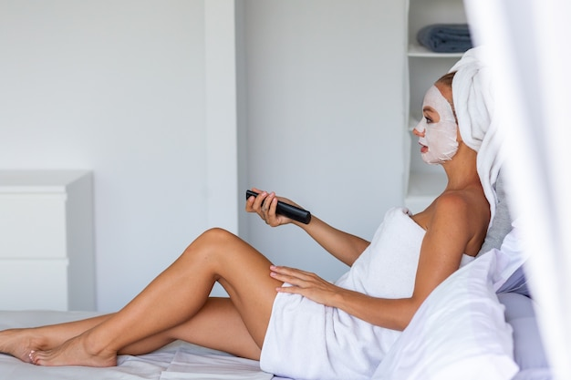 Портрет спокойной кавказской красивой женщины с полотенцем на голове и патчами маски для глаз на лице концепция ухода за кожей лица женщина расслабляется на кровати дома Бесплатные Фотографии