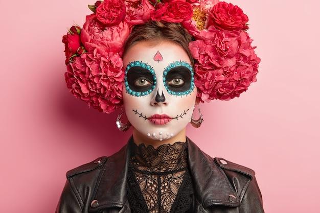 穏やかな女性の肖像画は死の日を祝い、砂糖の頭蓋骨の化粧、目の近くのくま、描かれた笑顔、死は人間の周期の自然な部分であると考え、伝統的なメキシコの服を着ています。 無料写真