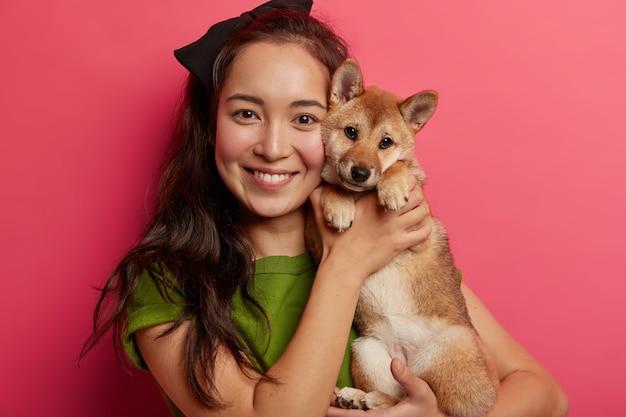Портрет заботливой женщины смешанной расы держит породистого щенка близко к лицу, обнимает собаку сиба-ину, хорошо проводит время, наслаждается домашним отдыхом, вечно вместе, отдыхает в студии. Бесплатные Фотографии
