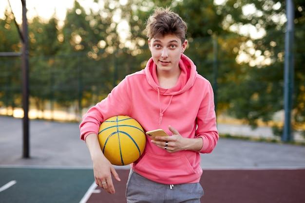 스마트 폰 및 손에 공을 백인 농구 선수 소년의 초상화 프리미엄 사진