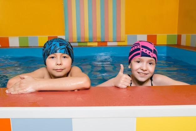 Портрет кавказского мальчика и девочки в бассейне Premium Фотографии