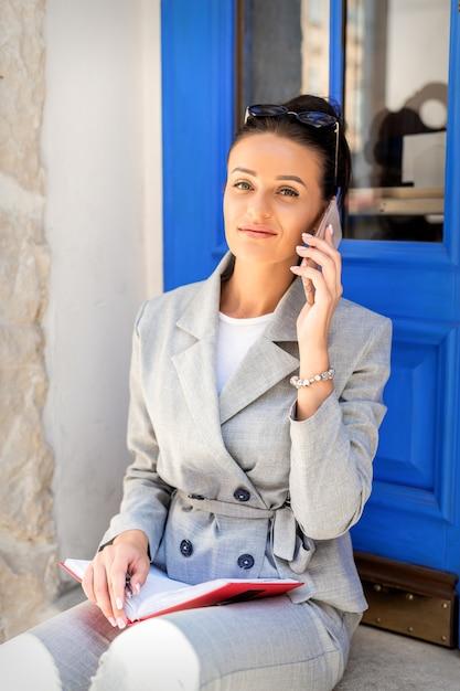 문에 회색 양복을 입고 휴대 전화에 백인 비즈니스 여자 회담의 초상화 프리미엄 사진