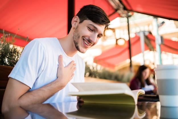 Портрет кавказского человека, наслаждающегося свободным временем и читающего книгу, сидя на открытом воздухе в кафе. концепция образа жизни. Бесплатные Фотографии