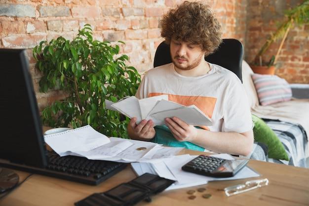 Портрет кавказского расстроенного и отчаявшегося человека, наблюдающего за финансово-экономическими графиками во время карантинного коронавируса, проблемы Бесплатные Фотографии