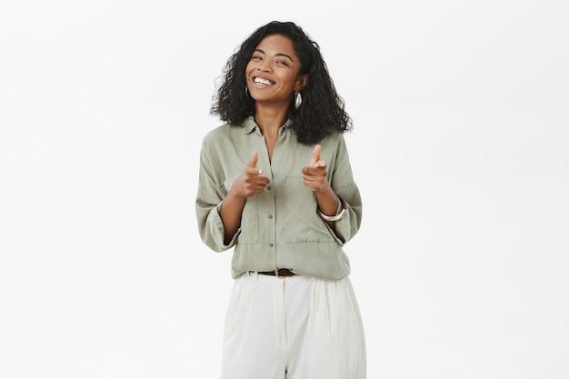 カリスマ的なフレンドリーで明るい魅力的な浅黒い肌の若い女性のブラウスとズボンを指で指している肖像画 無料写真