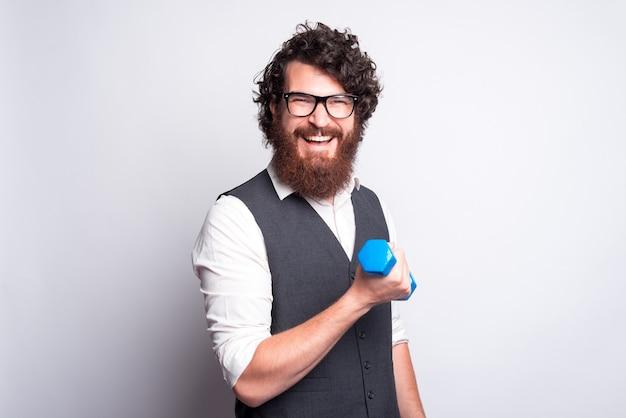 灰色のスーツを着て、青い小さなダンベルで作業している魅力的で面白いひげを生やした男の肖像画 Premium写真