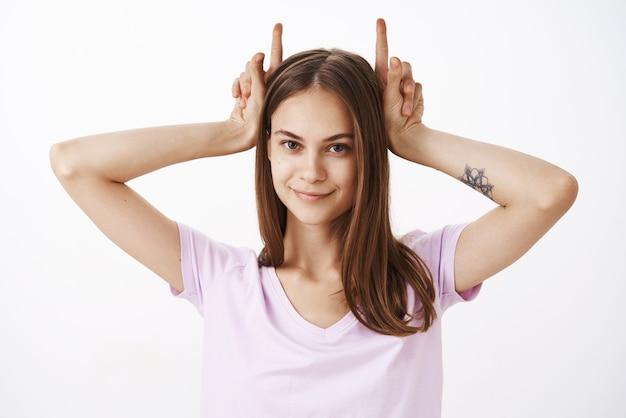 悪魔の角のような人差し指を頭に抱え、興味をそそられて喜んでいる顔に笑みを浮かべて腕に入れ墨を持つ魅力的なかわいいと自信を持ってヨーロッパの女性の肖像画 無料写真