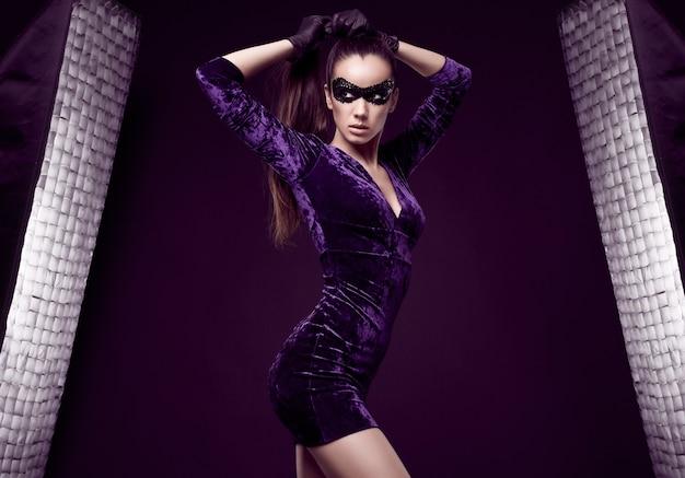 美しい紫色のドレスとスパンコールマスクの魅力的なエレガントなブルネットの女性の肖像画 無料写真