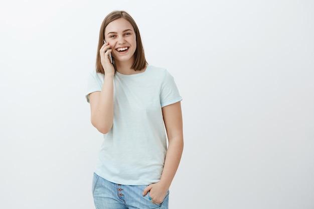 白い壁に面白がって魅力的な幸せと娯楽の女性の肖像画耳の近くのスマートフォンの呼び出しと話を面白がって 無料写真