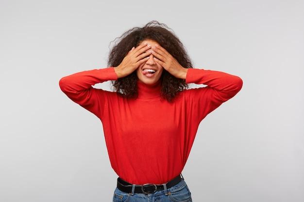 手のひらで目を覆い、喜びから広く笑っているアフロの髪型を持つ魅力的な幸せな女性の肖像画 無料写真
