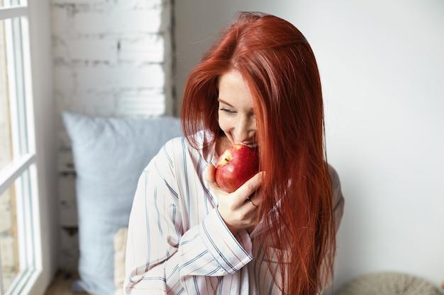 매력적인 즐거운 빨간 머리 젊은 유럽 여자의 초상화, 행복 한 표정을 가진 유행 스트라이프 잠옷을 입고, 신선한 잘 익은 빨간 사과를 물고, 아침에 과일을 먹고, 그녀의 방에있는 창가에 앉아 무료 사진