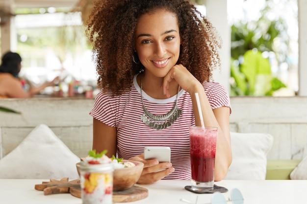 縮れた髪の陽気な暗い肌の女性の肖像画、スマートフォンのネットワークのブログ、夕食の休憩、高速インターネットに接続されているカフェでエキゾチックな料理を食べています。女性がメッセージを送る 無料写真