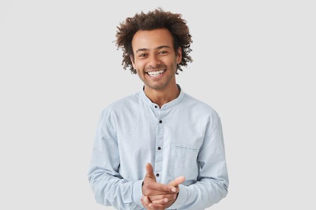 陽気なハンサムな男の肖像画は、エレガントなシャツを着て、手をつないで、広く笑顔、 無料写真